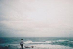 Homem em pé na beira do mar de costas olhando as ondas quebrarem