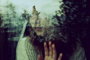 Garota triste com mão apoiada na janela