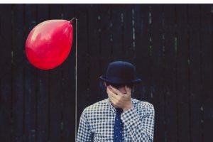 Homem segurando balão vermelho com mão no rosto e chapéu