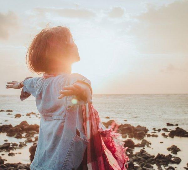 Mulher com os braços abertos de frente para o mar no fim de tarde.