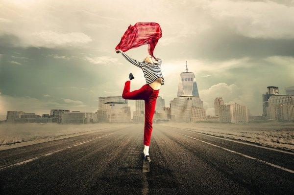 Mulher com a perna direita levantada para trás, e os braços inclinados para trás segurando um lenço vermelho.