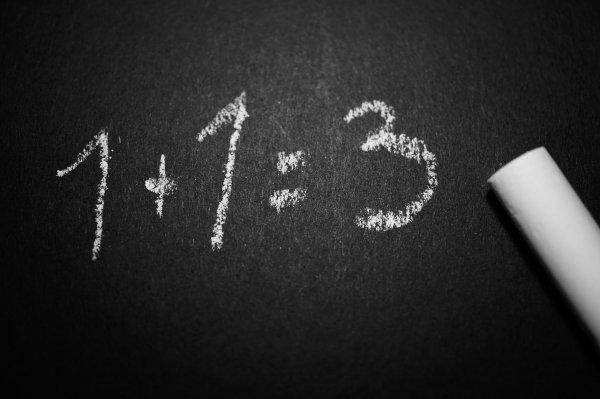 A equação 1+1=3 escrita com giz branco em uma lousa preta.