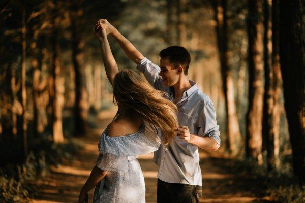 Casal dançando entre árvores. O homem está girando a mulher.
