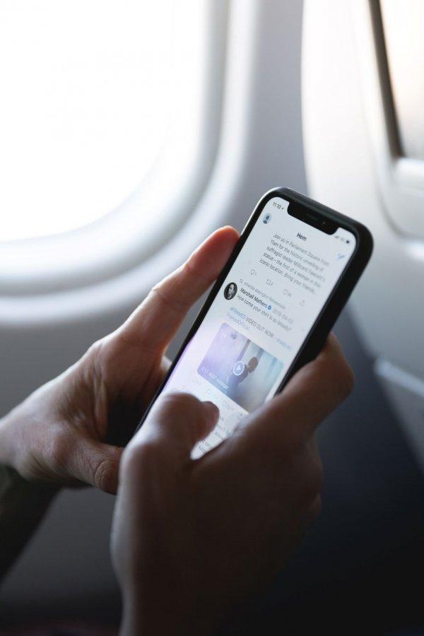 Pessoa em um avião usando o aplicativo do Twitter em seu smartphone.