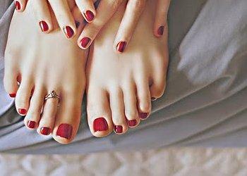 Pés e mãos femininos com as unhas pintadas.