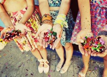 Mãos com confetes coloridos e fantasias de carnaval vistas de cima