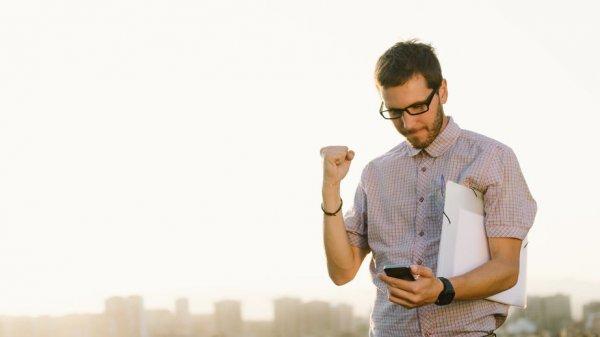 Homem comemorando com o punho direito fechado, segurando seu celular com a mão esquerda e uma pasta embaixo do braço.