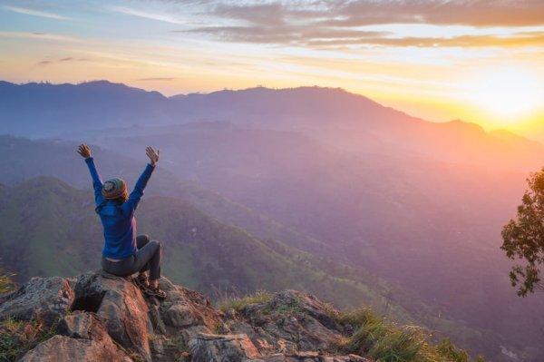 Mulher sentada em topo de montanha, olhando para um vale, com as duas mãos para o alto.