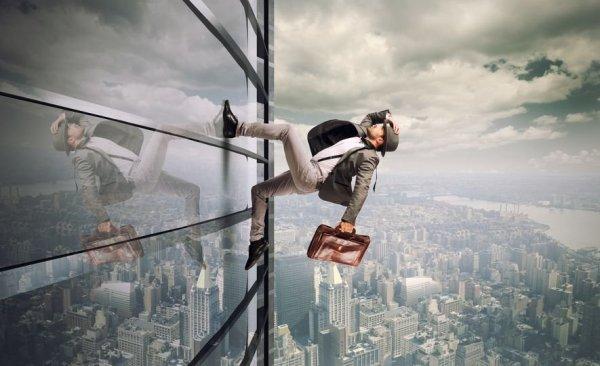 Homem com roupa social, segurando uma maleta com a mão esquerda e um chapéu em sua cabeça com a mão direita, corre na lateral de um arranha-céu, escalando-o.