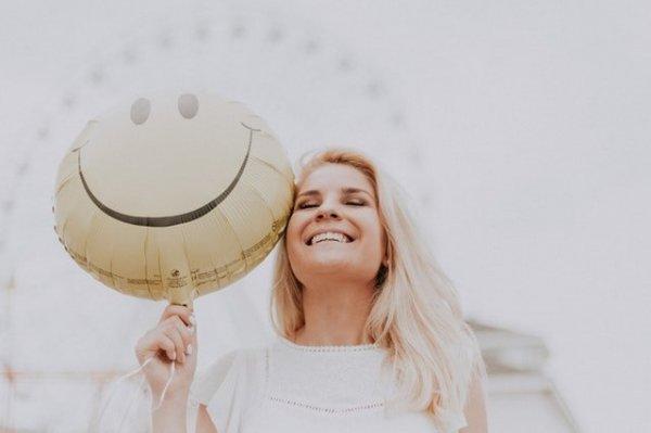 Mulher sorrindo de olhos fechados, segurando ao lado de seu rosto um balão amarelo redondo com uma carinha feliz desenhada.