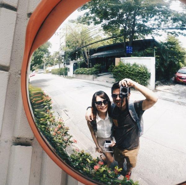 Casal tirando foto em um espelho na rua