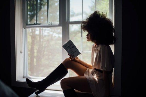 Mulher sentada em janela lendo um livro.