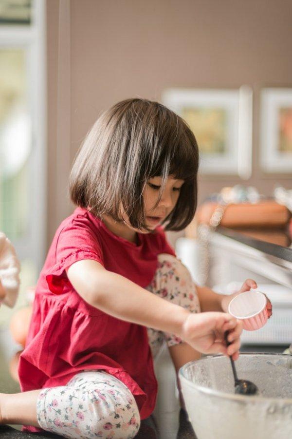 Criança em cima do balcão de uma cozinha, colocando massa de bolo em um pequeno recipiente.