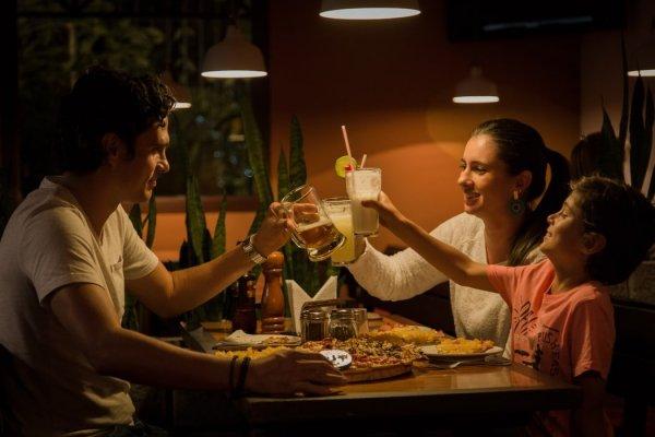 Família de pai, mãe e filho criança brindando suas bebidas em um restaurante.