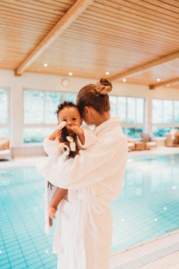 Mulher de roupão segurando um bebê no colo, em frente a uma piscina de spa.