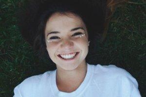 Menina sorrindo deitada na grama