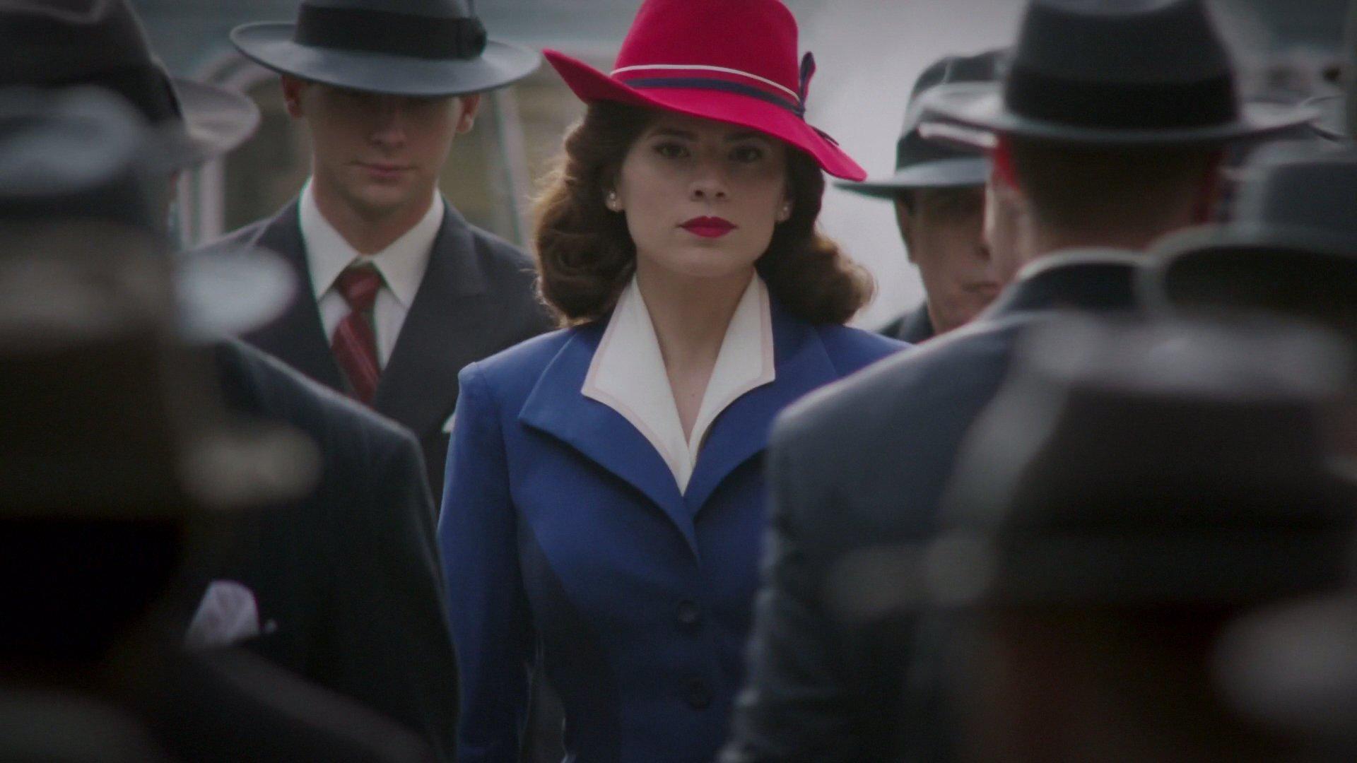 Protagonista da série andando entre multidão, com casaco azul e chapéu vermelho.