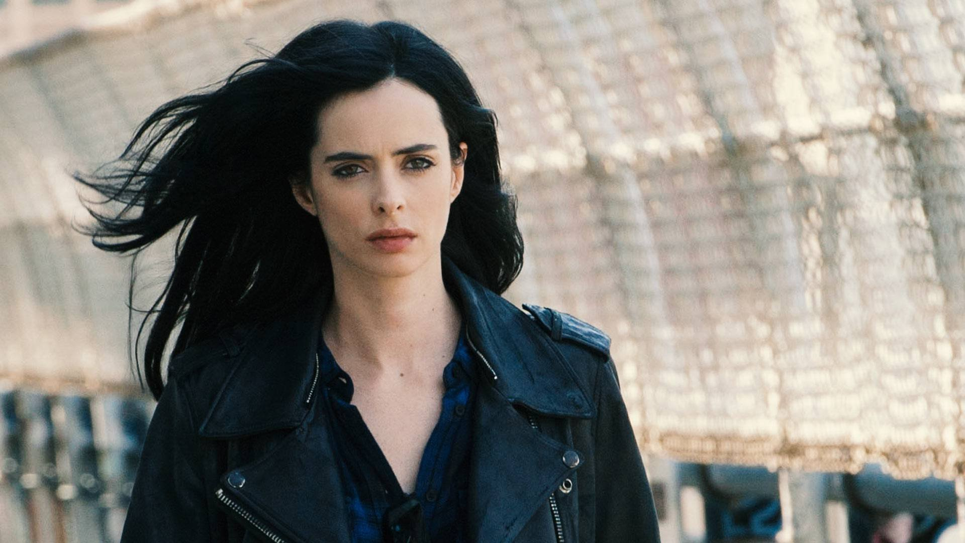 A protagonista da série, andando em um túnel, com o vento em seus cabelos e expressão séria.