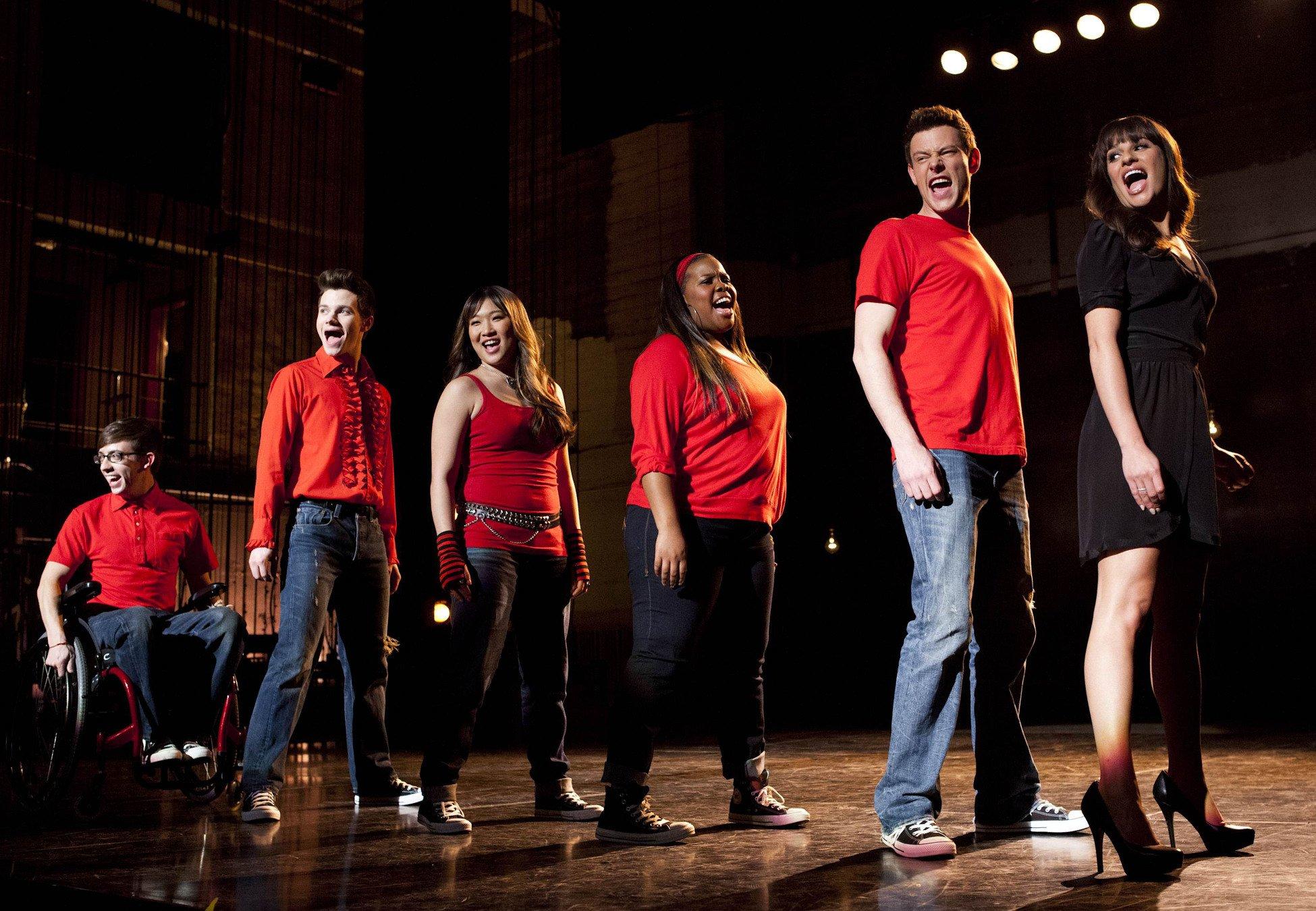 Elenco da série se apresentando em um palco.