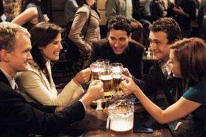 Personagens da série em uma mesa de bar, brindando com canecas de cerveja.
