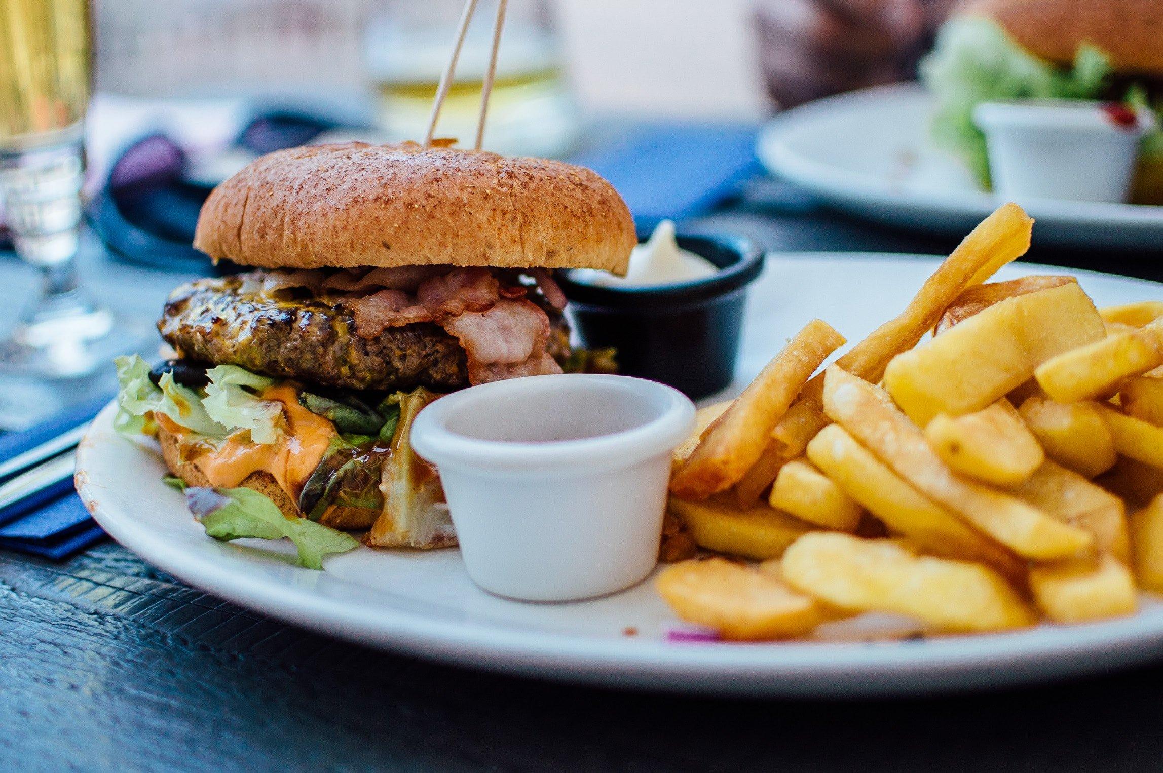 Foto de hambúrguer com porção de batatas fritas.