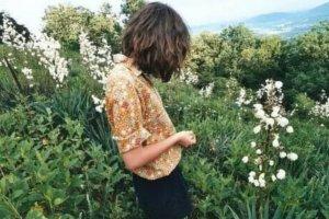Menina em meio a plantas e flores