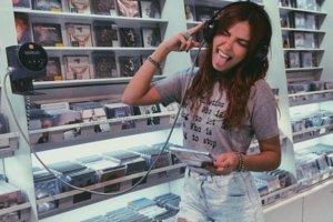 Mulher ouvindo música em loja de CDs