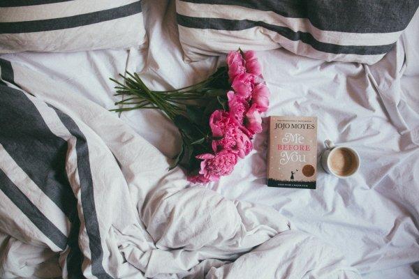 Cama com um buquê de flores rosas, um livro e uma caneca de café com leite.