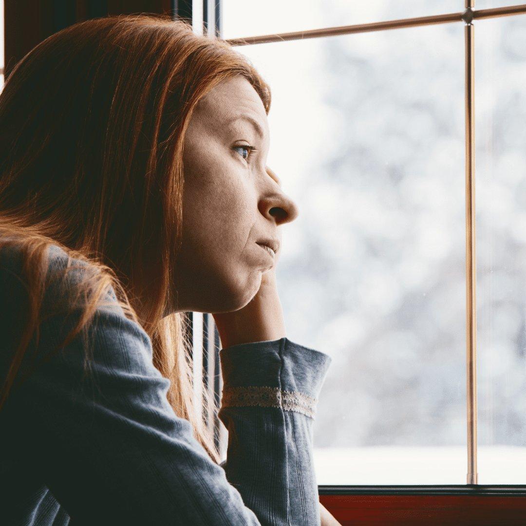 Mulher olhando pensativa pela a janela