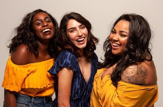 Três mulheres sorrindo uma ao lado da outra