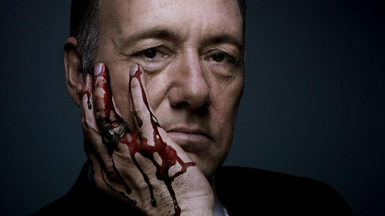 Kevin Spacey como Frank Underwood, apoiando seu rosto em sua mão direita, que está suja de sangue.