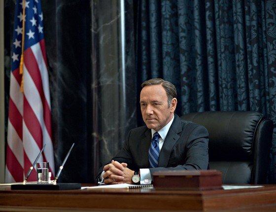 Kevin Spacey como Frank Underwood, vestindo terno e gravata, com as mãos entrelaçadas em cima de uma escrivaninha. Uma bandeira dos Estados Unidos está como decoração no fundo, ao lado esquerdo.