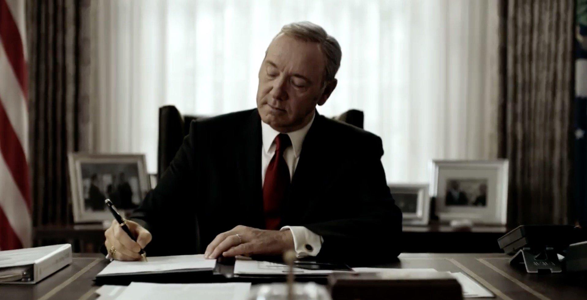 Kevin Spacey como Frank Underwood, vestindo terno e gravata, assinando um documento em seu escritório.