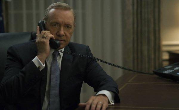 Kevin Spacey como Frank Underwood, vestindo terno e gravata, com o braço esquerdo apoiado em uma mesa, e a mão direita segurando um telefone em seu ouvido.