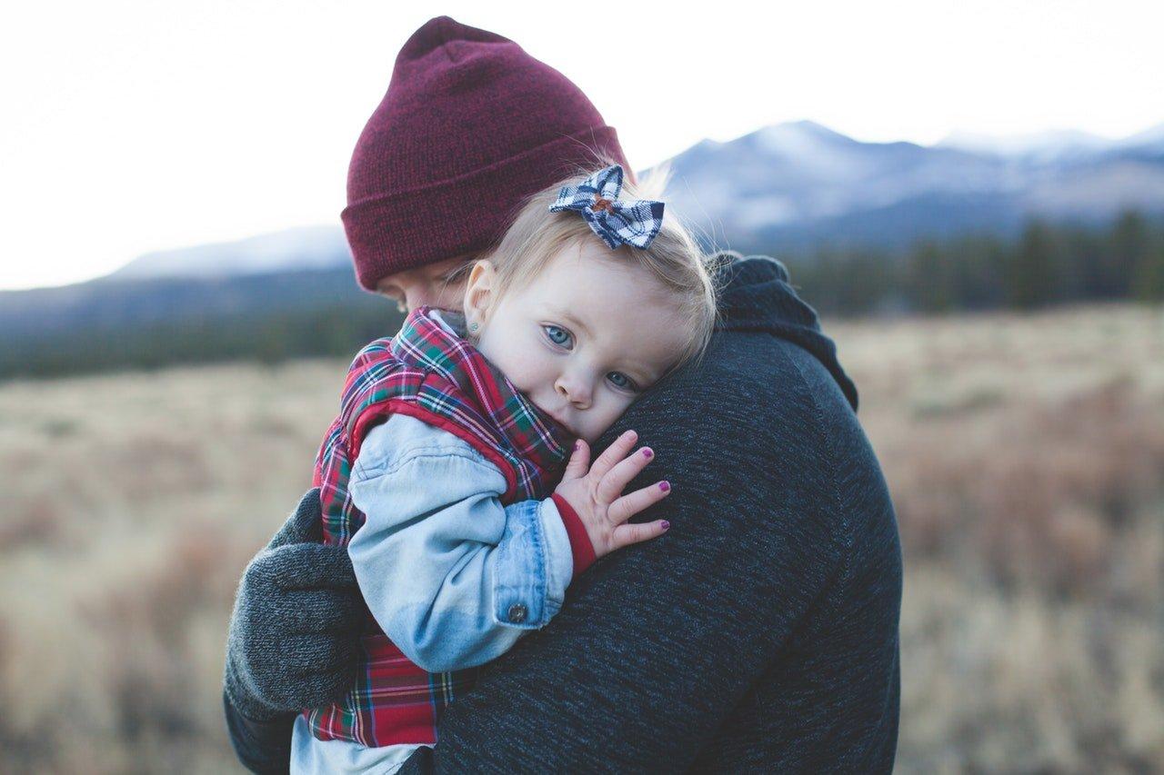 Bebê em colo de homem. A bebê está olhando para a câmera, enquanto o homem está com os olhos fechados e a cabeça encostada no ombro dela.