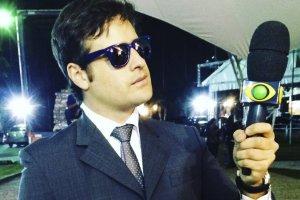 Rodrigo Scarpa, como Repórter Vesgo, no programa 'Pânico na Band', usando óculos escuro, terno, gravata e segurando um microfone.