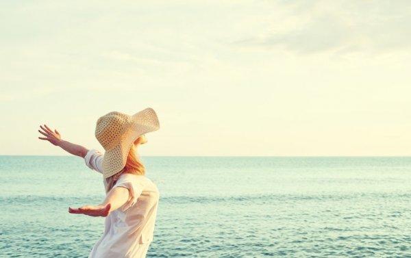 Mulher em praia com braços abertos