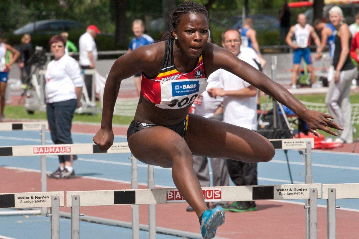 Mulher pulando barreira durante corrida de obstáculos.
