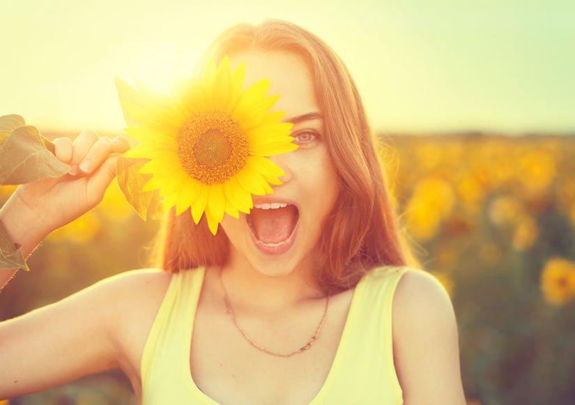 Garota com girassol em frente ao rosto e campo de girassol ao fundo com sol reluzindo