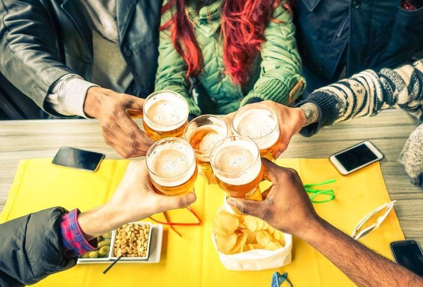Braços brindando com copo de cerveja visto de cima