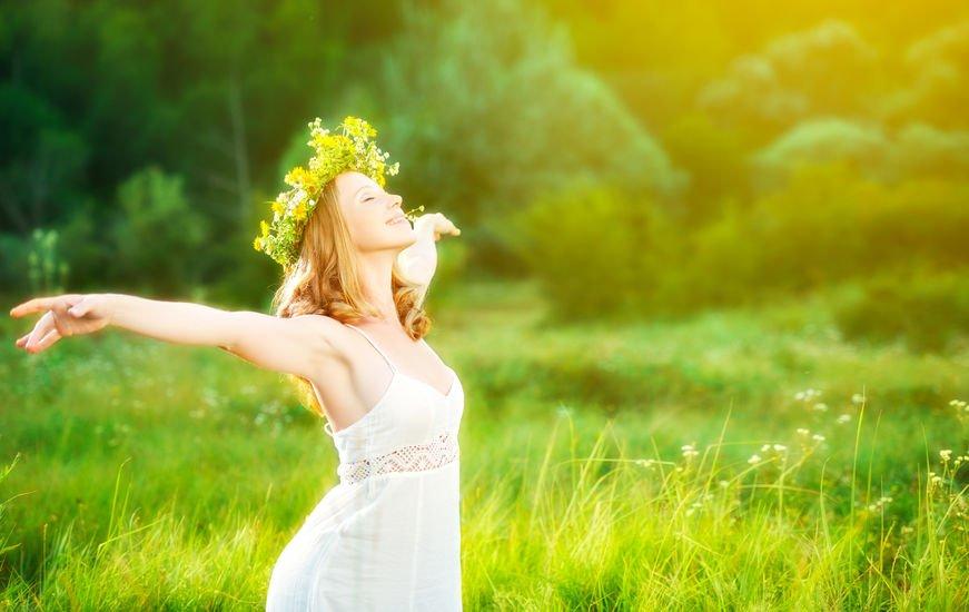 Mulher com braços abertos e coroa de flor na cabeça com fundo ver ao fundo e luz do sol