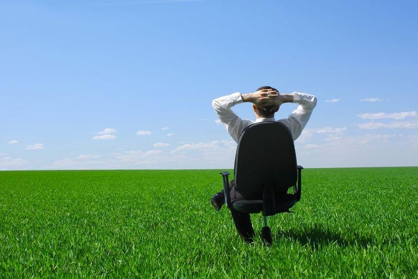 Homem sentado em cadeira de escritório em campo verde com céu azul ao fundo