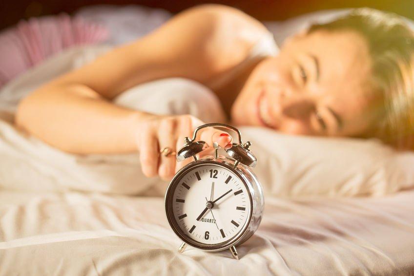 Mulher sorrindo na cama apertando botão de relógio em cama