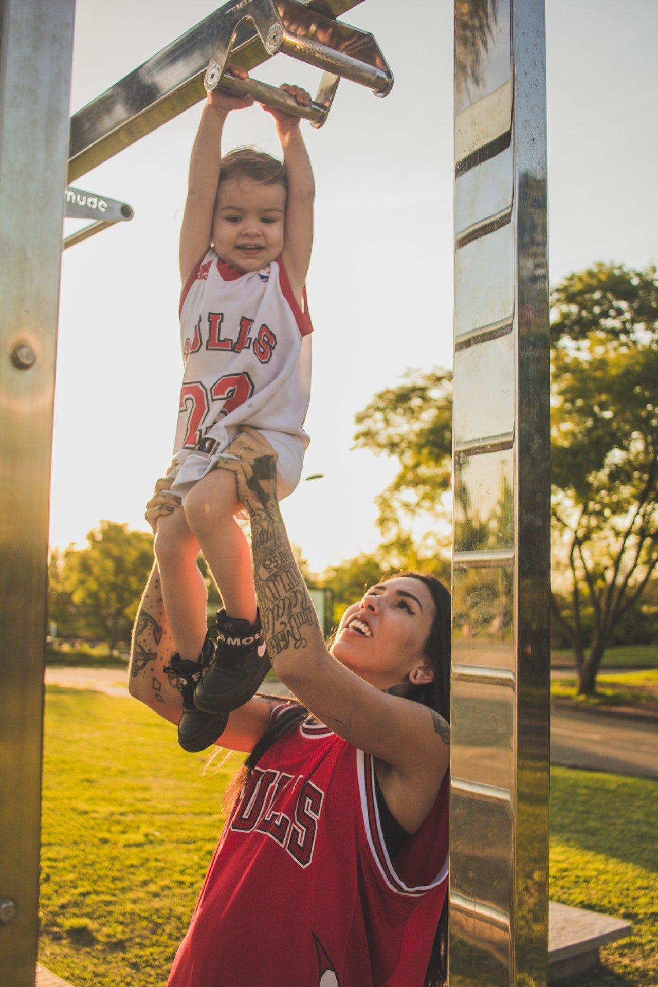Mulher segurando bebê para o alto pelas pernas, para que ele consiga alcançar um equipamento de ginástica no alto. Ambos usam uniforme de time de basquete.