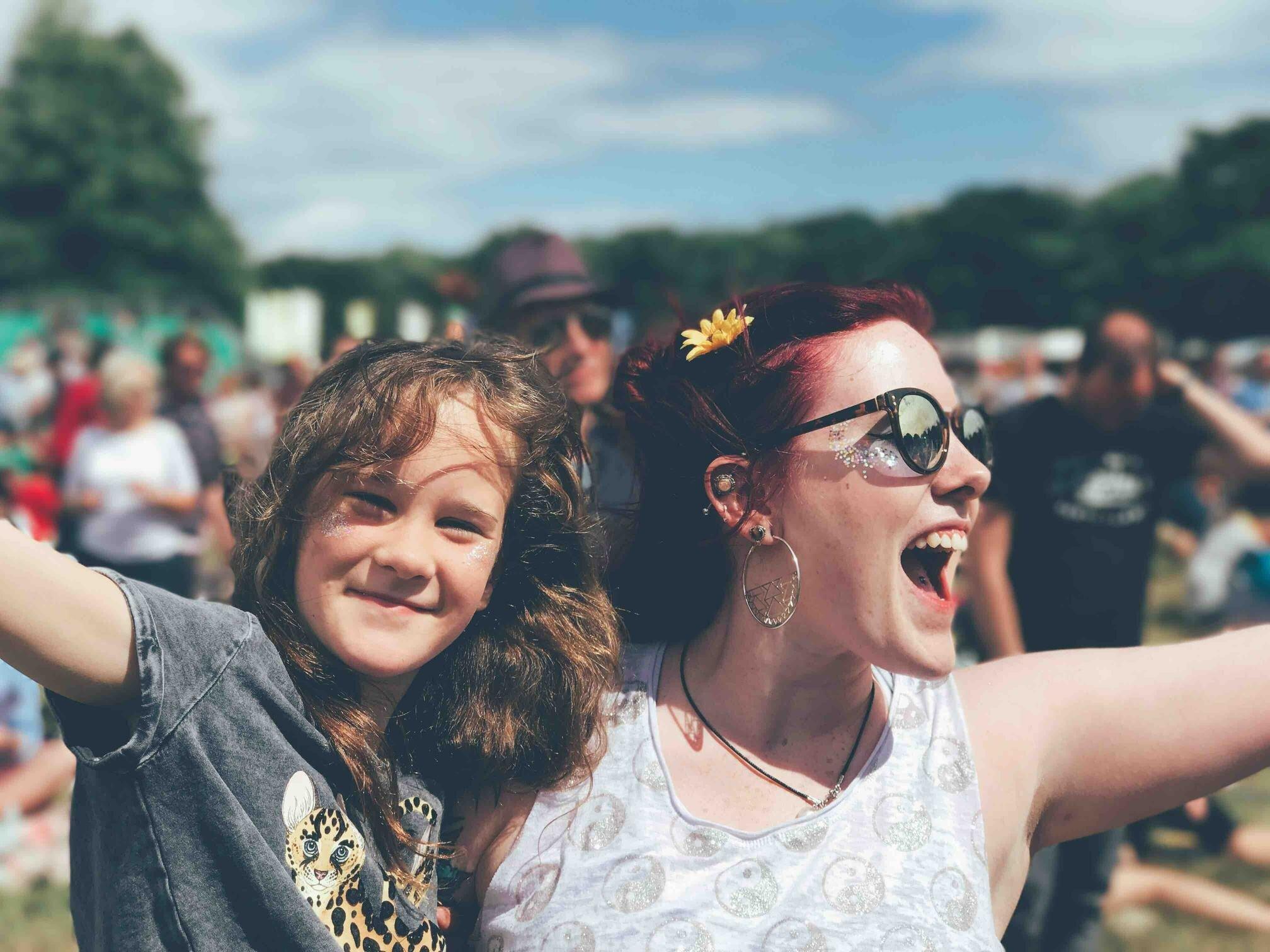 Menina e mulher lado a lado, de braços abertos e sorrindo, durante um festival.