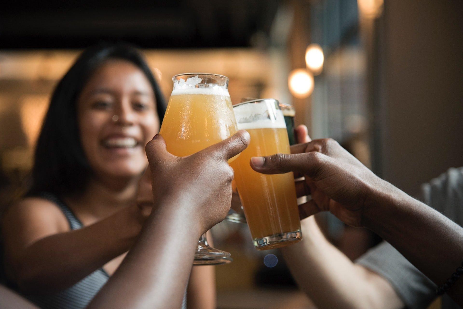 Pessoas brindando com copos de cerveja.