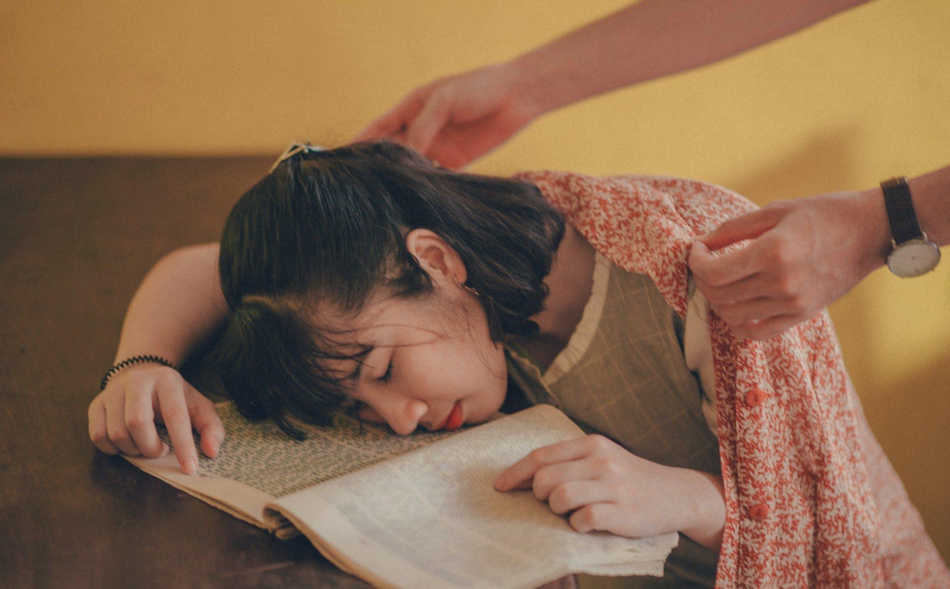 Pessoa cobre mulher que dormiu em cima de um livro na mesa.