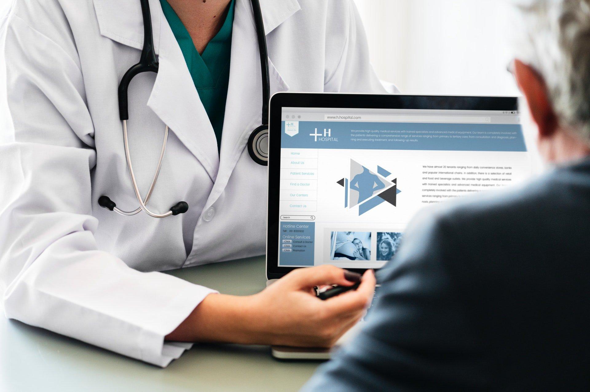 Médico mostrando página na Internet para seu paciente
