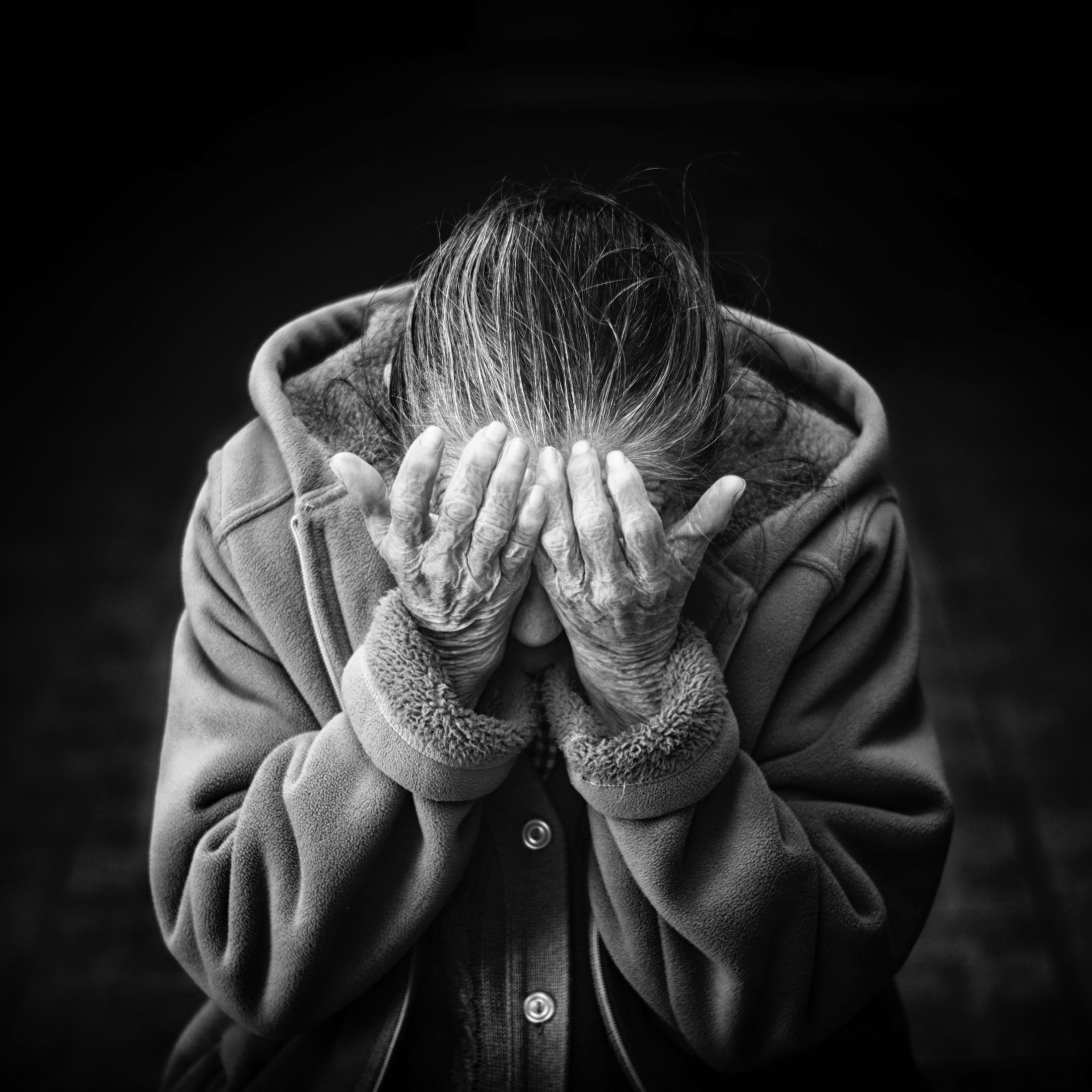 Imagem de uma idosa com as mãos na cabeça