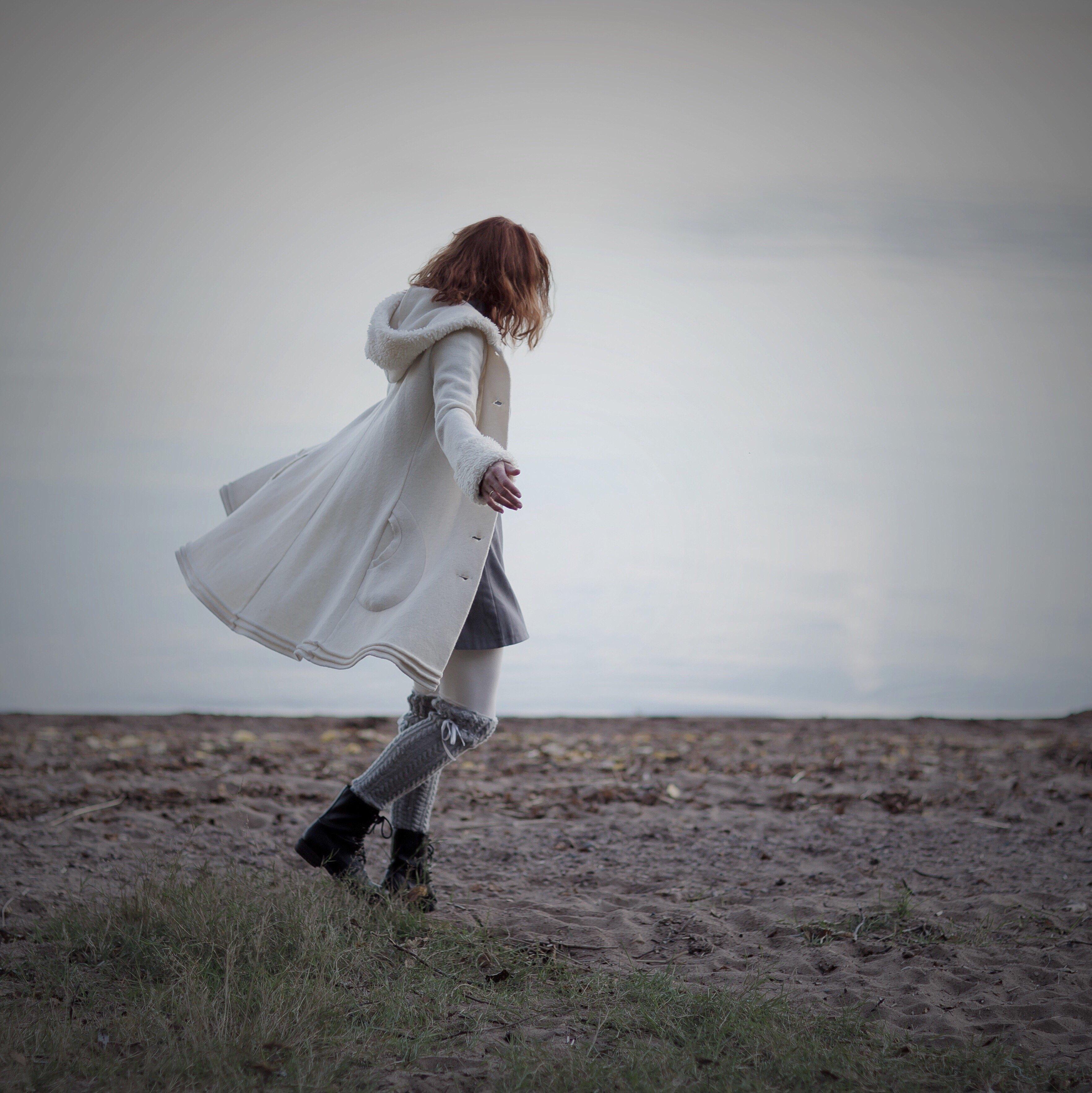 Mulher andando em gramado usando sobretudo e botas